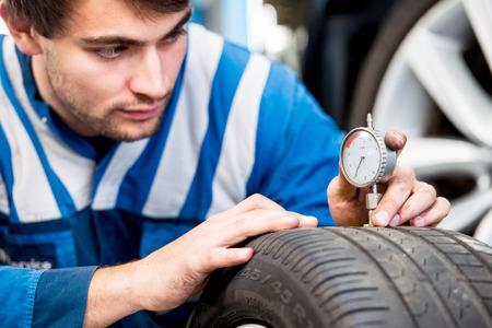 rodamiento: Mecánico, comprobando una galga de medición para comprobar la profundidad de la banda de rodadura de un neumático de coche para el desgaste, para asegurarse de que todavía está dentro de los reglamentos y seguro de usar. Centrarse en las manos y el indicador
