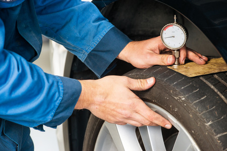 depth measurement: Mechanic, pressing a gauge into a tire tred to measure its depth for vehicle and road safety