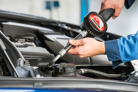 servicing: A modern sedan gets an oil change by a mechanic, using an electronic dosage system.