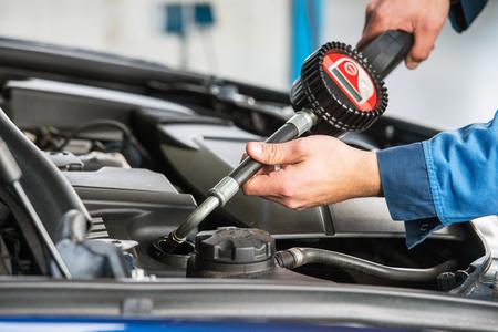 aceites: Un sedán moderno consigue un cambio de aceite por un mecánico, utilizando un sistema de dosificación electrónica.