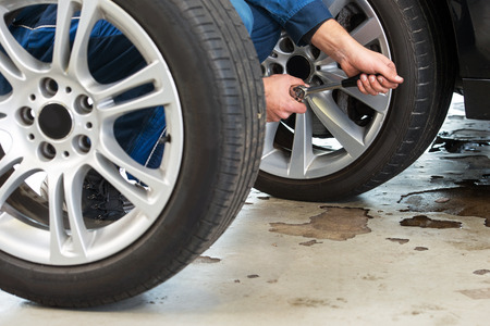 winter tires: A mechanic tightening the wheel nuts on an alloy light weight rim afhter having exchanged summer tires for winter tires Stock Photo