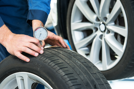 safety wear: Mechanic, pressing a gauge into a tire tred to measure its depth for vehicle and road safety