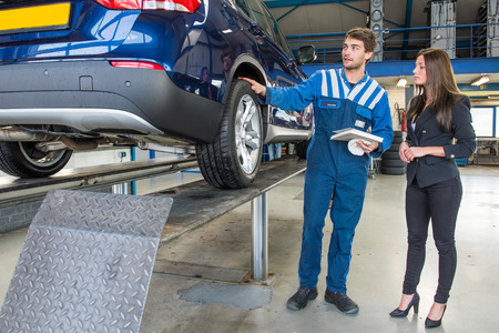 winter tires: Dedicated and professional service mechanic, showing a customer around her car, which has just been serviced and equipped with winter tires. The mechanic is holding a cloth to polish away stray spots and a work request form