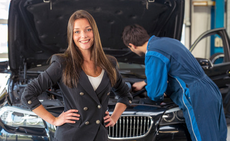 maintaining: Young woman waits for the car mechanic to fix maintenance and on her car in a garage Stock Photo