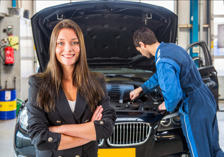 tends: Young business woman, smiling and looking into the camera, whilst a mechanic tends to the maintenance of her car in the background at a dedicated professional garage