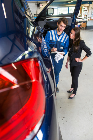servicing: Service mechanic showing a customer the bill of materials and work, don in servicing and repairing her car