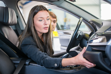 second hand: Young woman, reaching for the glove compartment at a garage, looking to buy a second hand car Stock Photo