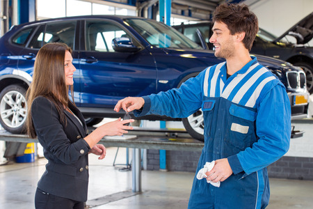 selling service smile: Young, pretty woman, receiving the keys of her new used second hand car from a service mechanic at a car dealer garage