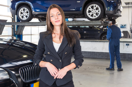 pleased: A pleased customer, posing in front of her justly fixed car at a high end garage, with a mechanic tending to another vehicle in the background Stock Photo