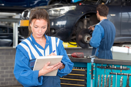 mot: Two mechanics at work in a garage. A woman in front checks off a maintenance sheet for periodic examination or mot test, with a man in the background, working on repairing and replacing a brake disk of a vehicle Stock Photo