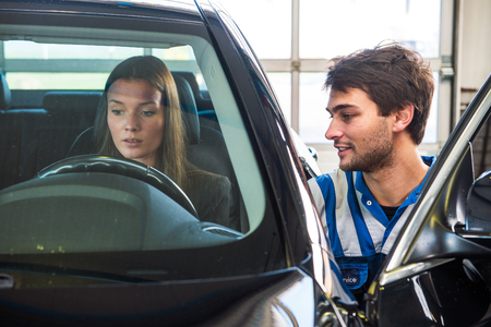 second hand: Young woman, behind the wheel of a second hand car, being assisted by a service mechanic, at a used car center