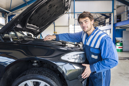 car in garage: Portrait of a smiling car mechanic looking under the hood of a car Stock Photo