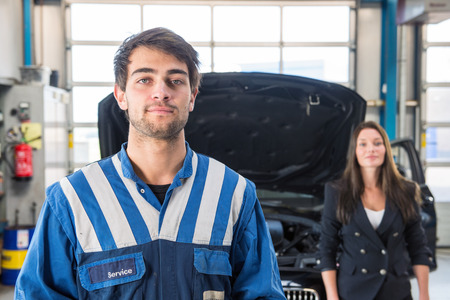 mot: Portrait of a young, professional, and confident mechanic, posing in front of a customer and her car with an open hood in a garage, wearing overalls