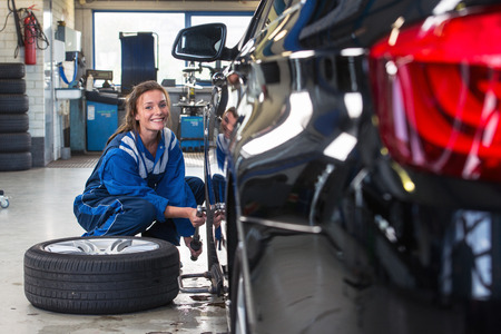 torque: Mechanic, a young woman changing the front tire of a black sedan using a torque wrench in a tire service center garage