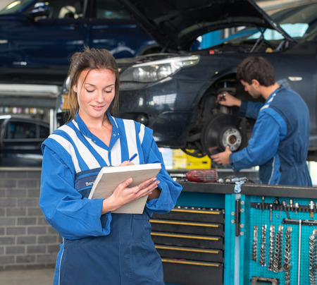mot: Two mechanics, working in a garage on a MOT test of a car, with a female mechainc in front, checking off inspection items on a  note block, with a tool trolley and her co-worker in the background