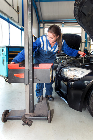 head light: Mechanic, using an advanced measturing tool, to adjust the hight of a head light beam and high beam of a car as part of a MOT test