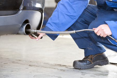 carbon emission: Mechanic, checking the exhaust fumes of a diesel fuelled passenger car for emission gasses, such as carbon dioxide.