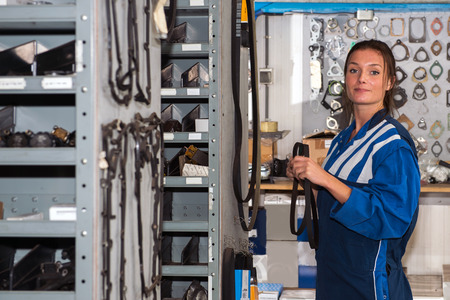shelfs: Female mechanic with a distribution belt in her hands in the storage room of a garage, filled with shelfs and racks with spare parts for car maintenance