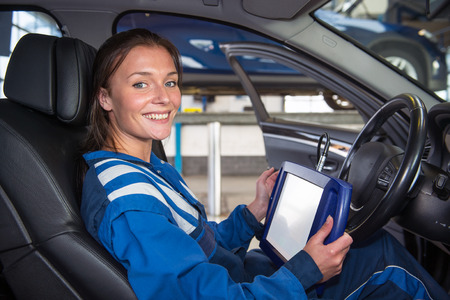 sturdy: Female mechanic, running a diagnostics program, connected to the computer of the cars, sitting in the drivers seat using a sturdy touch screen terminal Stock Photo