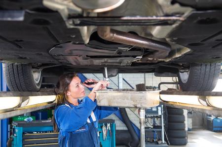 mecanico: Mecánico Fremale chaning el aceite de un vehículo en un elevador de coches, usando una llave de torsión para desenroscar el depósito de aceite. Un recipiente de recogida se coloca debajo de la salida con fines medioambientales y de reciclaje