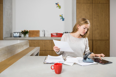 Young woman with documents and digital tablet calculating finance at table