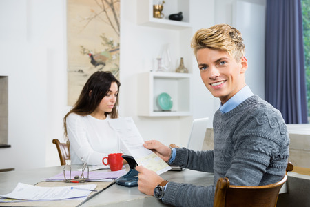 personal finance: Portrait of happy young man with woman calculating personal finance at home Stock Photo