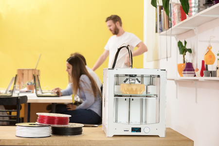 rapid prototyping: 3D printer with products on counter with designers working in background at creative studio Stock Photo