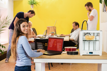 rapid prototyping: Portrait of happy young female designer using laptop by 3D printer with colleagues in background at studio Stock Photo