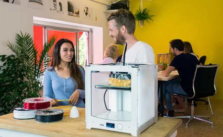 degradable: Male and female designers discussing at desk in 3D printing studio
