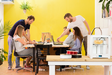 rapid prototyping: 3D printer machine with products on counter with designers working in background at creative studio Stock Photo