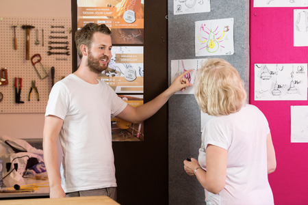 rapid prototyping: Male and female 3D designers discussing over charts in printing studio