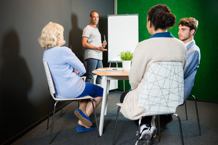 informal: Businessman giving presentation to colleagues in modern office lobby
