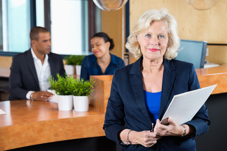 reception: Portrait of confident businesswoman holding file while receptionists working at counter in office Stock Photo