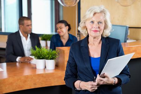recepcion: Retrato de confianza empresaria expediente de explotación, mientras que los recepcionistas de trabajo en el contador en la oficina Foto de archivo