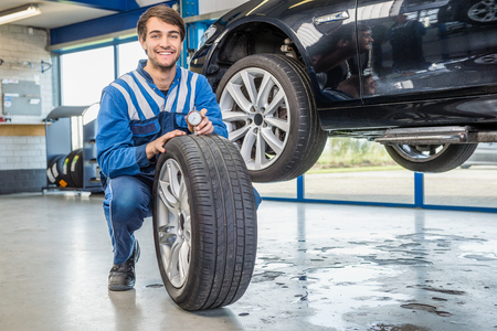 Portrait of happy male mechanic pressing gauge into tire tread to measure its depth at garage