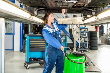 mecanico: Mec�nico de sexo femenino que repara el coche en el elevador hidr�ulico en la tienda de autom�viles