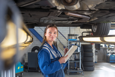 exhaust system: Young female mechanic, checking off test results underneath a car during a periodic safety test or MOT test