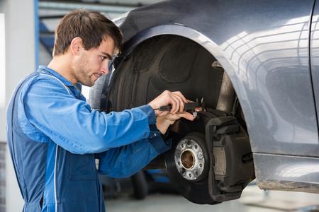 frenos: Mecánico masculino examinar disco de freno con pinza en el garaje