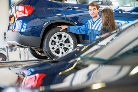 car in garage: Young mechanic discussing with female customer while standing by car in garage Stock Photo
