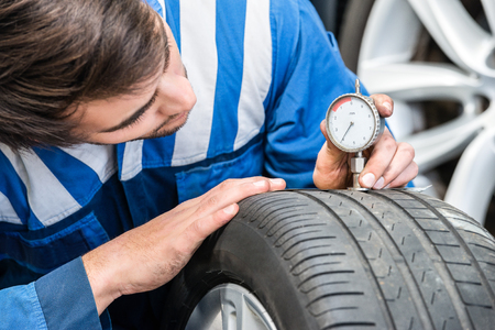 treads: Mechanic pressing gauge into tire tread to measure its depth in garage