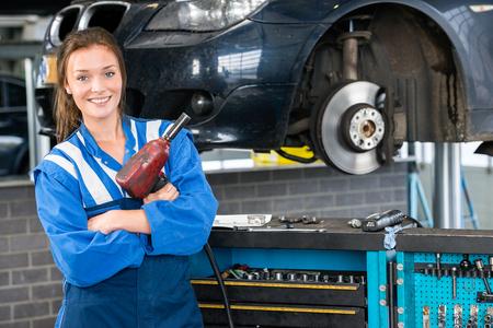 Portrait of happy female mechanic with pneumatic wrench standing by car in garage Zdjęcie Seryjne