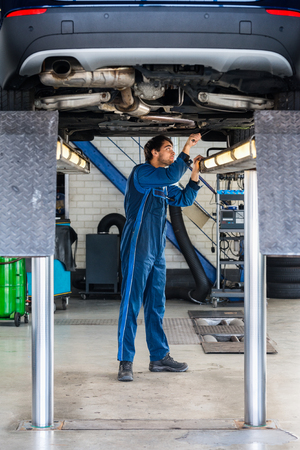 lift: Full length of male mechanic examining under the car at garage