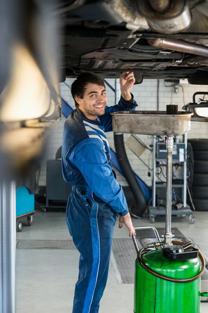 Portrait of smiling male mechanic repairing car on hydraulic lift in garage