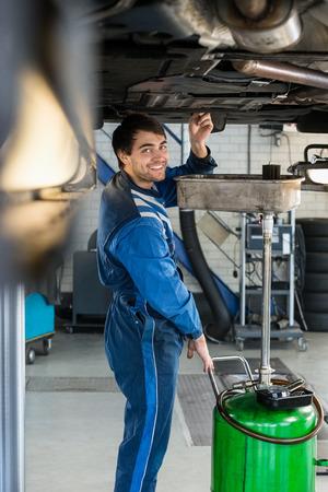 mecanico: Retrato de mec�nico de sexo masculino que repara el coche sonriente en ascensor hidr�ulico en el garaje Foto de archivo