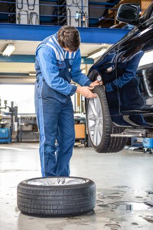 depth gauge: Male mechanic pressing gauge into tire tread to measure its depth at garage at garage