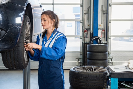 tire repair shop: Female mechanic changing tire from suspended car at auto shop