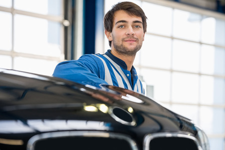 shop skill: Portrait of confident young mechanic standing by car in garage Stock Photo