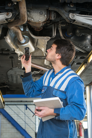muffler: A mechanic, checing a muffler on an exhaust system of a modern car on a car lift using a LED flashlight, for gas leaks during a periodic inspection or MOT test