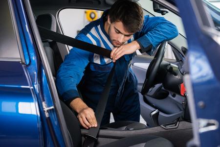 shop skill: Male mechanic examining car seat belt in garage
