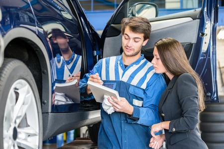 Car mechanic with female customer going through maintenance checklist in garage